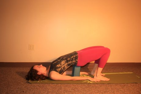 Supported Bridge: Use your block under your sacrum for a more restorative version of the posture. Remember, the higher you place the block, the deeper you will get into your backbend.