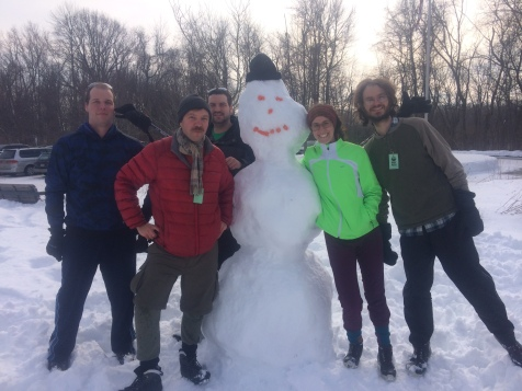 My friends and I by our snowman after many hours of cross country skiing.